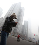 Beijing. Сhina - January 23, 2013: Unidentified woman with mask walking on circa January 2013 in , China.China's cities face serious air pollution as the Stock Photo
