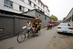 Beijing local people riding the tricycles, guiding foreigners for a Hutong tourism Stock Image