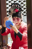 Beijing opera actress makeup and comb hair. Beijing opera female actor with traditional headwear making up, getting ready for performance stock images