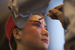 Beijing opera makeup. The Beijing opera actress is being painted the scenic mask on her face Royalty Free Stock Photos