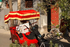 Beijing Rickshaw driver having a break while waiting for tourists royalty free stock photography