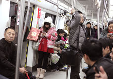 Beijing subway. Beijing, Сhina - January 24, 2013: Girl surrounded with people in Beijing subway.The Beijing Subway's single-day ridership record of 8.69 Stock Photography