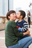 Beijo do bebê sua mãe em sua cara fotos de stock royalty free