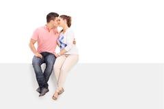 Beijo do homem e da mulher assentado em um painel Imagens de Stock