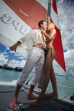 Beijo dos pares de Gorgerous, estando no barco de vela, catamarã abaixo Imagens de Stock