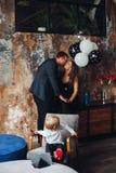Beijo, filho dos pais sentando-se na cadeira e olhando para trás neles imagens de stock