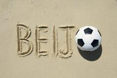 Beijo-Kuss-Mitteilung im Sand mit Fußball Stockbild