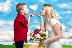 Beijos bonitos novos do sopro da mãe e do filho Uma mulher e um menino com um ramalhete, uma cesta das flores Conceito da mola do Foto de Stock Royalty Free