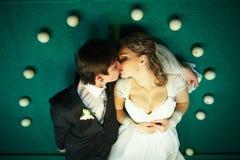 Beijos dos pares na tabela de bilhar cercada com bolas brancas imagem de stock