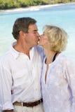 Beijos maduros felizes de um par na praia foto de stock