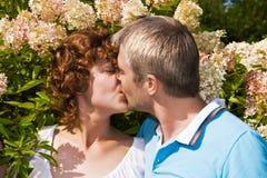 Beijos novos dos pares no flores Fotos de Stock Royalty Free