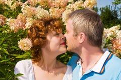 Beijos novos dos pares no flores Fotografia de Stock Royalty Free