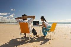 Beiläufige Arbeitskräfte, die am Strand sich treffen Lizenzfreie Stockfotos