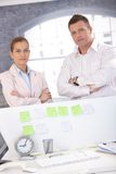 Beiläufige Büroangestellte, die hinter Schreibtisch stehen Lizenzfreie Stockfotos