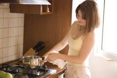 Beiläufige Frau, die auf Ofen kocht stockbild