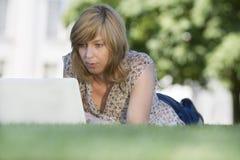 Beiläufige Frau, die draußen Laptop verwendet Stockfoto