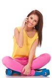 Beiläufige Frau ist, sprechend sitzend und am Telefon Lizenzfreie Stockfotos
