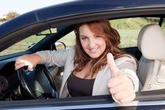 Beiläufige Geschäftsfrau, die auf einem Auto lächelt Stockbild
