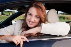 Beiläufige Geschäftsfrau, die auf einem Auto lächelt Lizenzfreie Stockfotografie
