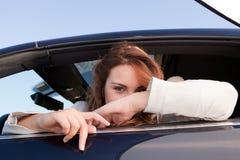 Beiläufige Geschäftsfrau, die auf einem Auto lächelt Stockfotos
