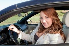 Beiläufige Geschäftsfrau, die auf einem Auto lächelt Lizenzfreies Stockbild