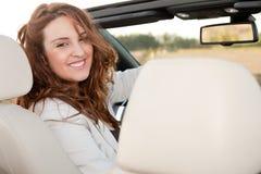 Beiläufige Geschäftsfrau, die auf einem Auto lächelt Stockfotografie