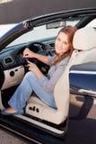 Beiläufige Geschäftsfrau, die auf einem Auto lächelt Lizenzfreie Stockfotos