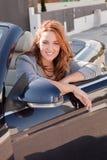 Beiläufige Geschäftsfrau, die auf einem Auto lächelt Stockfoto