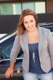 Beiläufige Geschäftsfrau, die auf einem Auto lächelt Stockbilder