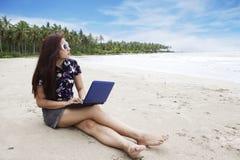 Beiläufige Geschäftsfrau, die an dem Strand arbeitet stockfotografie