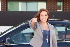 Beiläufige Geschäftsfrau, die mit einer Autotaste lächelt Lizenzfreie Stockbilder