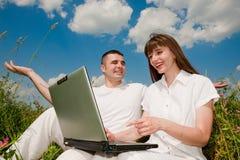 Beiläufige glückliche Paare auf einer Laptop-Computer draußen Stockfotografie