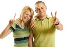Beiläufige Paare, die ihr Siegzeichen bilden stockbild