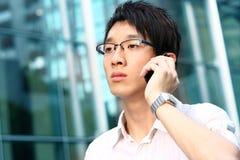 Beiläufiger asiatischer Geschäftsmann, der auf seinem Handy spricht Lizenzfreies Stockfoto