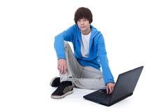 Beiläufiger Jugendlichjunge, der auf dem Fußboden sitzt Stockbilder