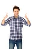 Beiläufiger junger Kerl, der sich Daumen zeigt stockbilder