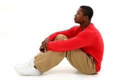 Beiläufiger junger Mann, der auf Fußboden sitzt Lizenzfreie Stockfotos