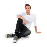 Beiläufiger Kerl, der auf dem Fußboden sitzt lizenzfreies stockfoto