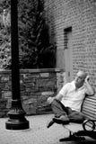 Beiläufiger Kerl, der auf einer Stadt-Bank sitzt Lizenzfreie Stockfotos