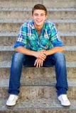 Beiläufiger Kerl, der auf Treppen sitzt Stockfotos