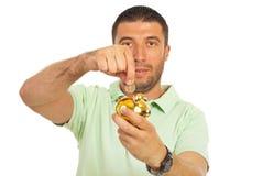 Beiläufiger Kerl setzte Münze in piggy Querneigung ein Stockfotos