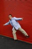 Beiläufiger Mann, der auf einem Fahrwerkbein balanciert Lizenzfreies Stockbild