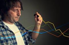Beiläufiger Mann, der ein steigendes Diagramm zeichnet Stockfotos