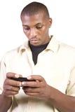 Beiläufiger schwarzer Mann Texting auf seinem Handy Lizenzfreies Stockbild