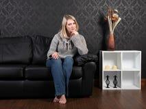Beiläufiges blondes Mädchenhaus, das auf lederner Couch sich entspannt Lizenzfreie Stockbilder