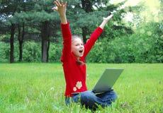 Beiläufiges Erfolgsmädchen auf einem Laptop in einem grünen Gras Lizenzfreies Stockbild