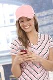 Beiläufiges Mädchen, welches das Mobiltelefonlächeln verwendet Stockbild