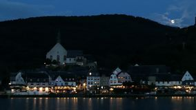 Beilstein都市风景在微明下与月光 汽车通过  流动在前面的摩泽尔河 股票录像