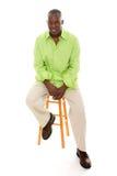 Beiläufiger Mann, der auf Schemel sitzt Stockbild