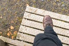 Bein, das über hölzernen Zauntritt tritt Lizenzfreie Stockbilder